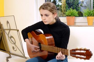 Musik-Schülerin spielt Gitarre