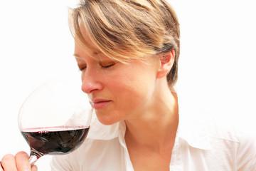 lächelnde Frau riecht am Rotwein