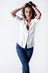 Fashion model in a blouse and jeans barefoot on a white backgrou
