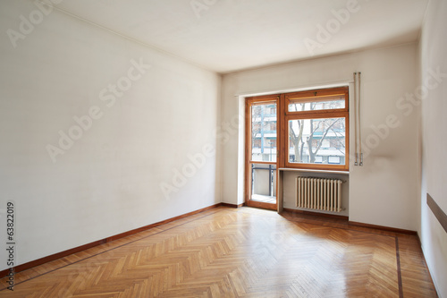 Empty room with wooden floor and dirty white walls