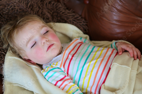 Cute toddler girl having day nap on the sofa