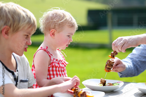 Family having healthy tasty bbq lunch outdoors