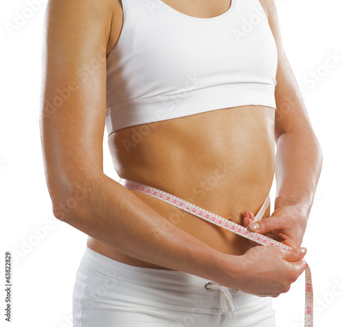 young athletic woman measuring waist
