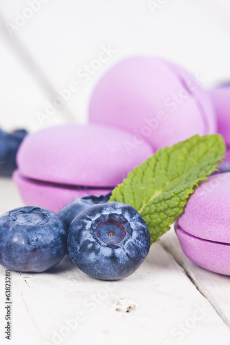 macaroons fresh blueberries on white wooden background