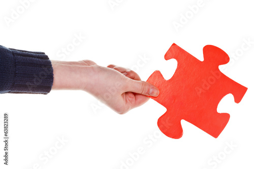 female hand holding big red paper puzzle piece