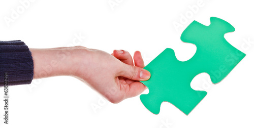 female hand holding big green paper puzzle piece