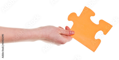 female hand holding big yellow paper puzzle piece