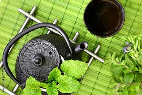 Tabletop with oriental teapot and cup with fresh herbs