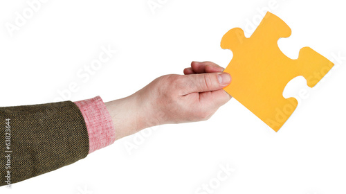 male hand holding big yellow paper puzzle piece