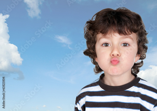 Funny child making grimace throwing a kiss