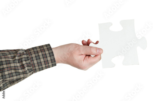 male hand holding big white paper puzzle piece