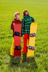 couple in sport wear with snowboards standing on the grass and w