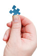male fingers holding jigsaw puzzle piece