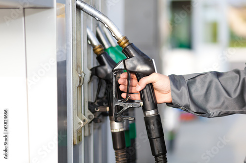 canvas print picture Man holding a fuel nozzle