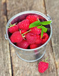 raspberries in a bucket on wooden surface