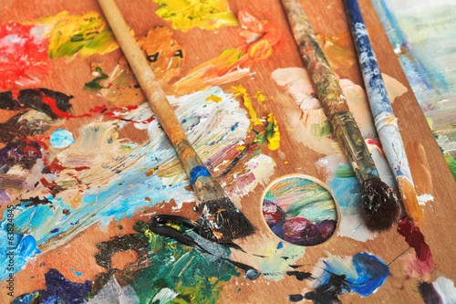 paintbrushes on wooden artistic pallette