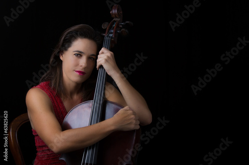 Beautiful brunette holding cello with selective light in red dre
