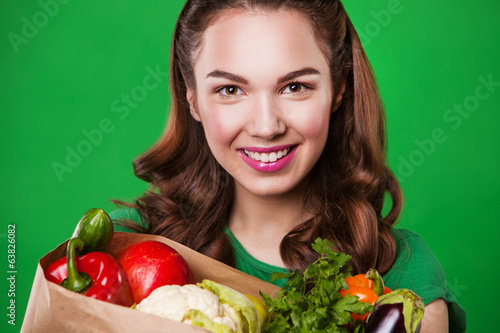 Young smiling woman with a fresh vegetables. on green