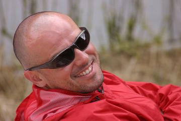 Joven calvo con gafas de sol sonriendo