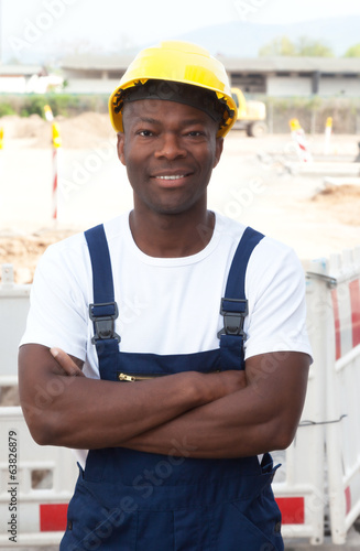 Friendly african construction worker with crossed arms