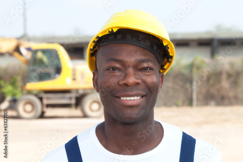 Laughing african worker at construction site with excavator