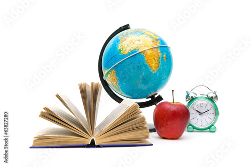 book, globe, apple and an alarm clock on a white background