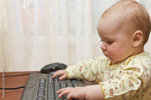 kid gets acquainted with a computer keyboard