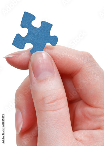 female fingers holding jigsaw puzzle piece