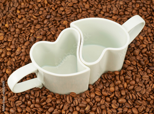 Two empty cups on coffee beans