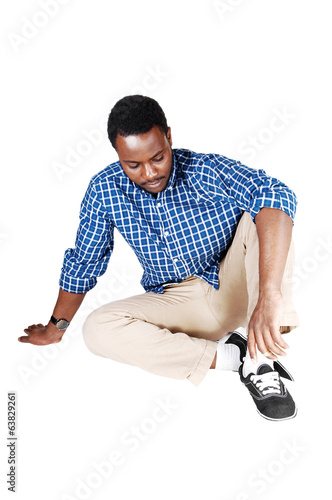Black man sitting on floor.