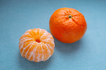peeled and whole tangerine on blue background
