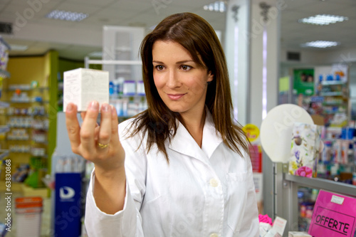 Beautiful female doctor in uniform holding medicine in pharmacy