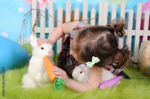 sweet toddler girl feeding bunny at easter