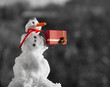 Little snowman with christmas gift box outdoor. Winter season.
