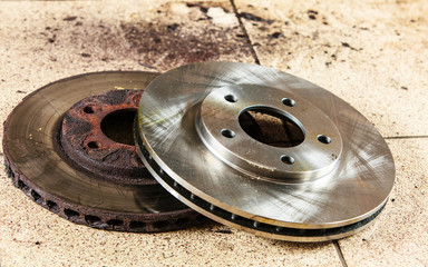Auto in service. New and old front brake disks for modern car.
