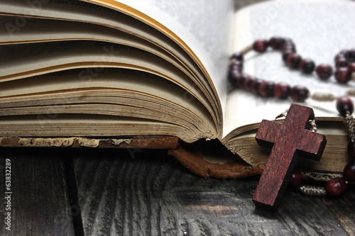 Rosary and old book on a wooden table