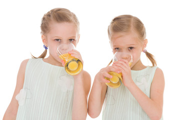 Cute sisters drink from a glass of fresh orange juice.