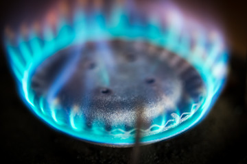 Blue flame gas stove in the dark. Selective focus.