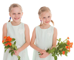 Two charming girls with bouquets of roses.
