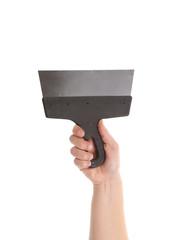 Hand holds metal spatula.