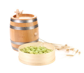 Wooden barrel and hops in basket.