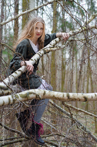 Picture of beautiful blonde girl sitting on birch branches