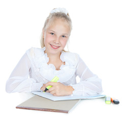 Young blonde girl drawing at the desk