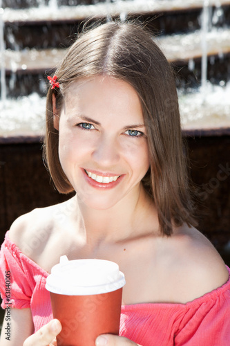 Young woman with a cup of coffee outdoors