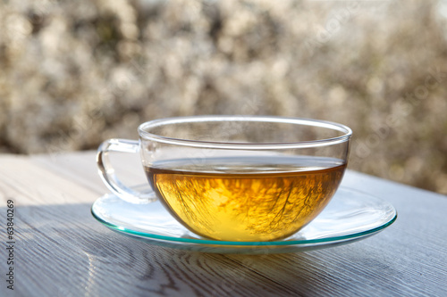 cups of tea on wooden table with blossoming cherry background