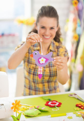 Closeup on happy young woman showing easter decoration