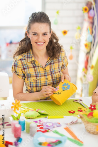 Portrait of happy young woman making easter basket in studio