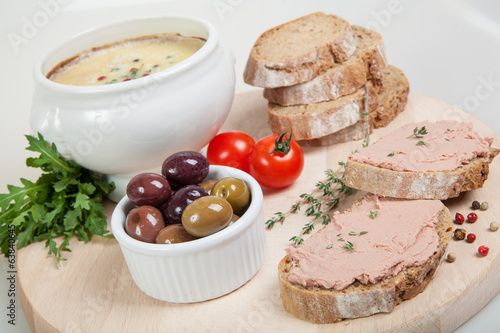 Homemade pate, olives, tomatoes and slices of bread on board