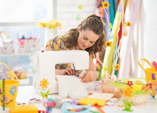 Young woman making easter pot holder mitts in studio