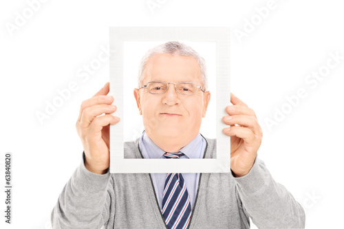 Senior man posing with frame in front of his face